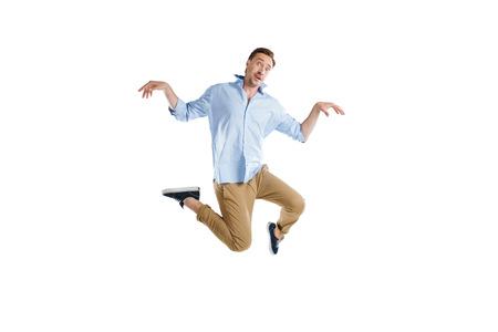 Foto de young casual man jumping with funny expression - Imagen libre de derechos