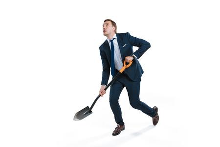 Foto de young businessman in formal wear digging with shovel and looking up - Imagen libre de derechos