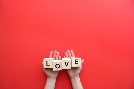 Foto de Human hands holding wooden cubes with love sign isolated on red background - Imagen libre de derechos