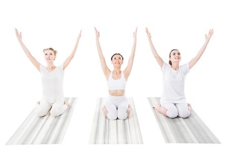 Foto de group of cheerful women practicing yoga on yoga mats - Imagen libre de derechos
