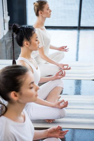 Foto de women with eyes closed meditating in lotus pose with gyan mudra indoors - Imagen libre de derechos