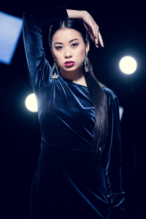 Photo for seductive asian woman posing in evening dress and diamond earrings and looking at camera at event with spotlights - Royalty Free Image