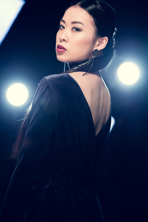 Photo for seductive asian woman in evening gown looking at camera at event with spotlights - Royalty Free Image
