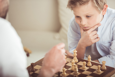 Foto de little boy playing chess together with father at home - Imagen libre de derechos