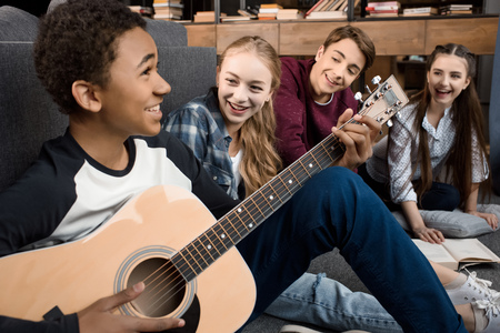 Photo for african american boy playing acustic guitar and singing while his friends listening at home - Royalty Free Image