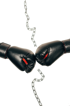 Foto de Pair of black boxing gloves with metallic chain in the middle isolated on white - Imagen libre de derechos