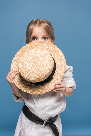 Foto de scared adorable little girl with straw boater - Imagen libre de derechos