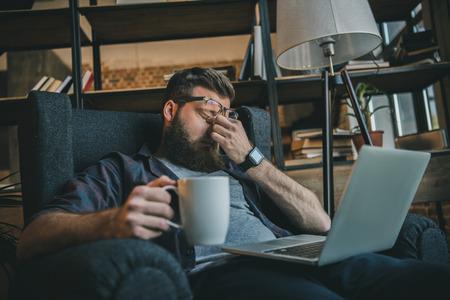 Foto de freelancer in eyeglasses using laptop and drinking coffee at home - Imagen libre de derechos