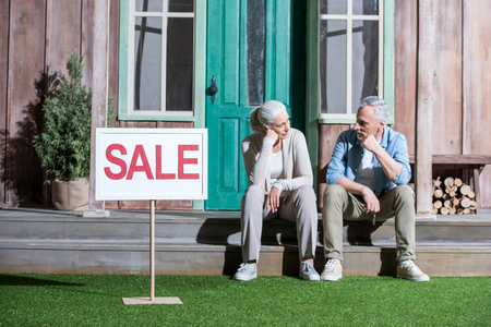 Foto de upset senior couple sitting on porch and selling their house - Imagen libre de derechos
