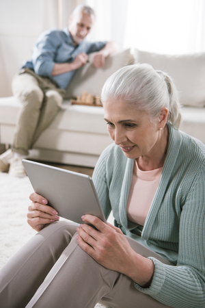 Photo for senior woman using digital tablet while her husband playing chess on sofa - Royalty Free Image