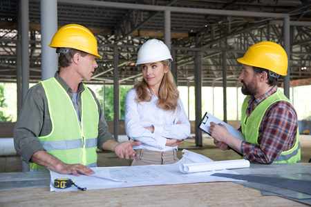 Photo pour builders and contractor talking during work on construction site - image libre de droit