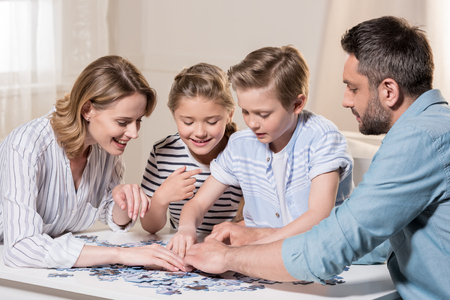 Photo pour family playing with puzzle on table at home together - image libre de droit