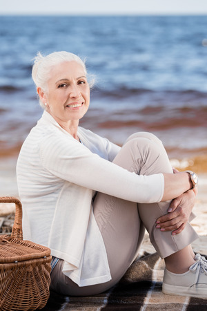 Photo for senior woman sitting on plaid with picnic basket and looking at camera - Royalty Free Image