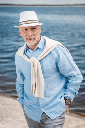 Photo for grey haired stylish man with hands in pockets at riverside - Royalty Free Image