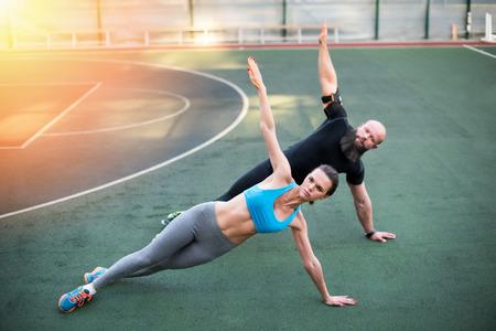 Photo pour couple doing side plank with raised hands on the stadium - image libre de droit