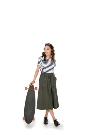 Photo pour hipster girl in skirt standing with skateboard and looking away - image libre de droit