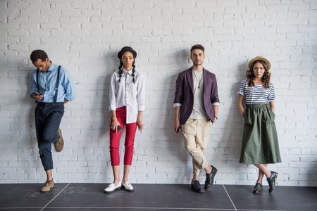 Foto de multiethnic friends posing in stylish clothes near brick wall - Imagen libre de derechos