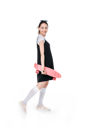Photo pour asian woman posing with skateboard isolated on white - image libre de droit