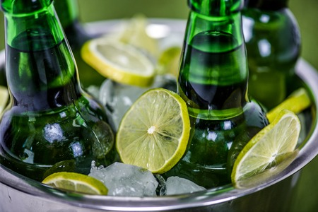 Foto de Closeup view of bucket with ice cubes, beer bottles and lemon slices - Imagen libre de derechos
