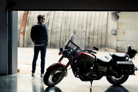 Photo for stylish young man in leather jacket standing near motorbike and looking away - Royalty Free Image