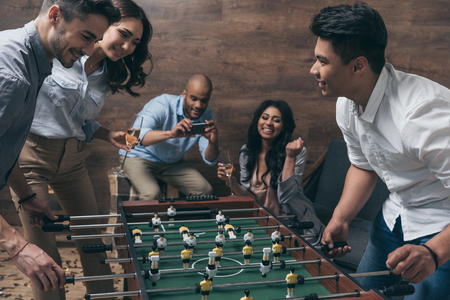 Foto de young friends playing table football together indoors - Imagen libre de derechos