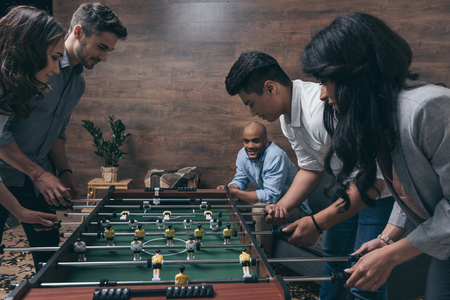 Photo pour young friends playing table football together indoors - image libre de droit