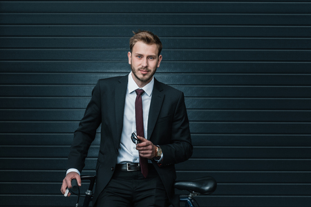 Photo pour young businessman sitting on bicycle and holding sunglasses - image libre de droit