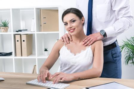 Photo pour businessman touching shoulders of his pretty colleague at workplace - image libre de droit