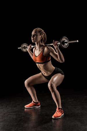 Photo pour young sportswoman lifting barbell and looking away - image libre de droit