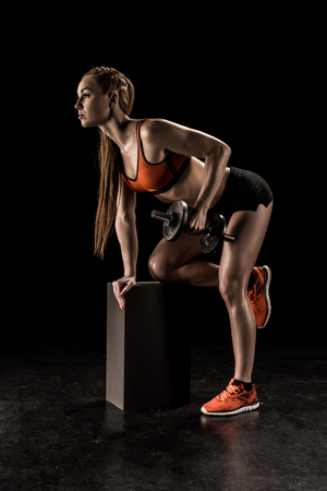 Photo pour muscular young sportswoman standing on knee and exercising with dumbbell - image libre de droit