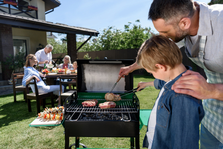 Foto de father and son grilling meat while family sitting at table outdoors - Imagen libre de derechos