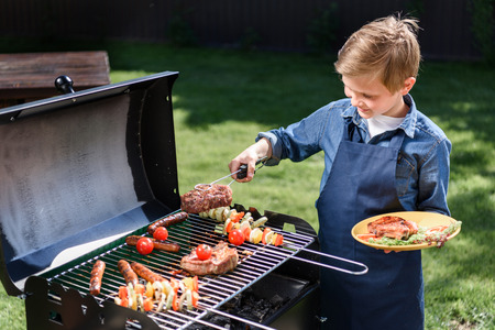 Photo for kid boy in apron preparing tasty stakes on barbecue grill outdoors - Royalty Free Image