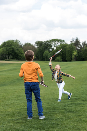 Photo pour brother and sister playing badminton on green grass - image libre de droit
