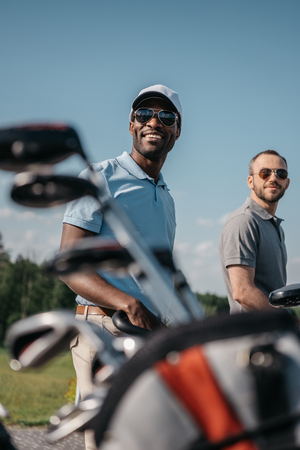 Photo for multiethnic sportsmen going to the golf course, bag with clubs on foreground - Royalty Free Image