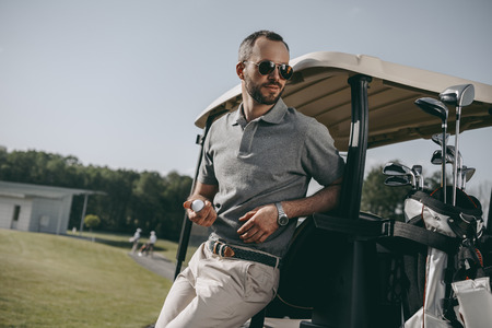 Photo for golfer holding golf ball and looking away while leaning on golf cart - Royalty Free Image