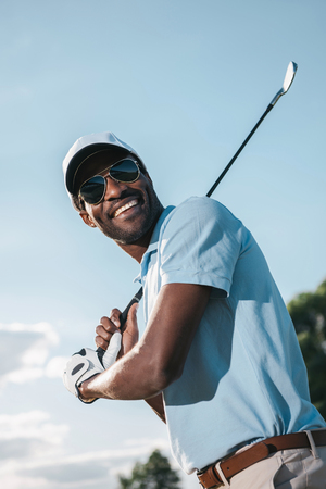 Photo pour african american man in cap and sunglasses holding club and playing golf - image libre de droit