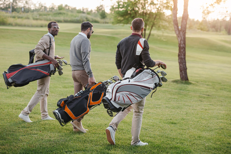 Photo for golf players with golf clubs in bags walking on golf course - Royalty Free Image