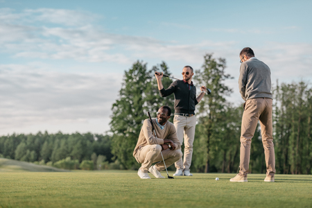 Foto de multicultural friends spending time together while playing golf on golf course - Imagen libre de derechos