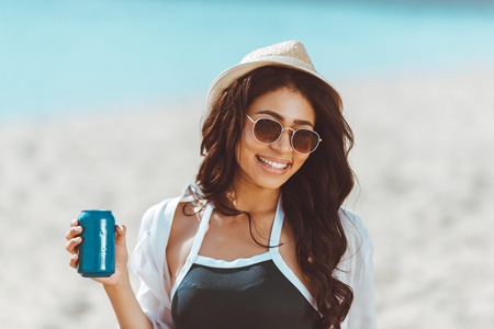 Foto de young woman in sunglasses and straw hat holding soda can and smiling at camera - Imagen libre de derechos