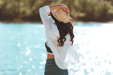 Photo pour young woman in straw hat standing on beach and looking at river - image libre de droit