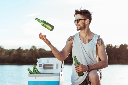 Photo pour casual man smiling while juggling bottles of beer on riverside - image libre de droit