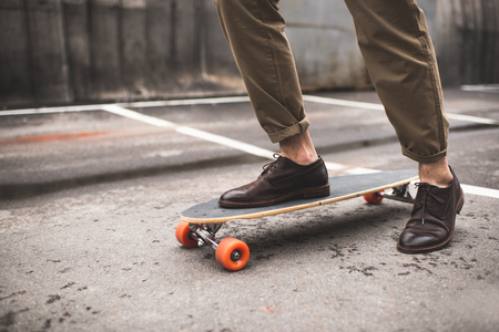Photo for low section of stylish man in leather shoes with longboard - Royalty Free Image