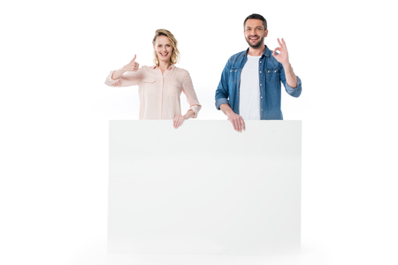 Photo for Happy young couple holding blank banner and gesturing successful sign - Royalty Free Image