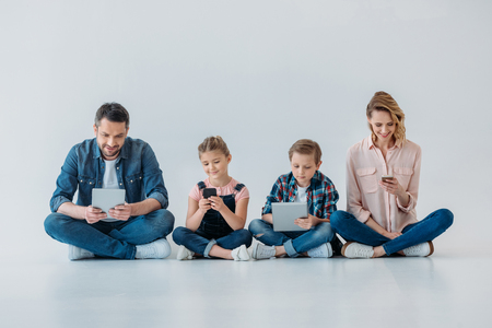 Photo pour family using digital devices while sitting on the floor - image libre de droit