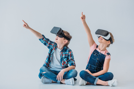 Foto per kids using virtual reality headsets and pointing up with finger while sitting - Immagine Royalty Free