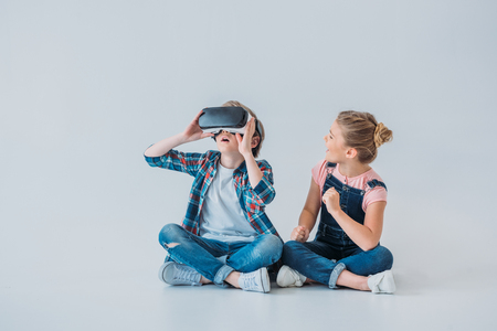 Foto de kids using virtual reality headset while sitting on the floor - Imagen libre de derechos