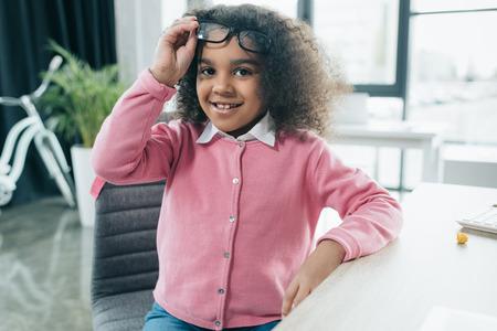 Foto de smiling african american girl with eyeglasses sitting in office - Imagen libre de derechos