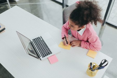 Photo pour african american girl using laptop and taking notes at table - image libre de droit