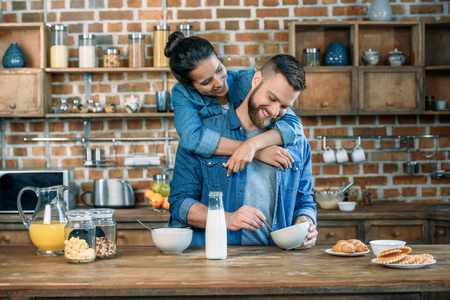 Photo for young woman hugging handsome bearded man having breakfast at home - Royalty Free Image