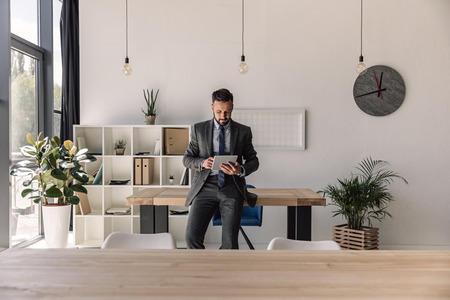 Photo pour bearded concentrated businessman using digital tablet in modern office - image libre de droit